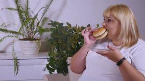 Mujer gorda que come una hamburguesa, una TV de observación y laughes Fotos de archivo libres de regalías