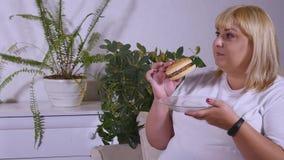 Mujer gorda que come una hamburguesa, una TV de observación y laughes Imágenes de archivo libres de regalías