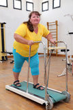 Mujer gorda que corre en la rueda de ardilla del instructor Imagenes de archivo