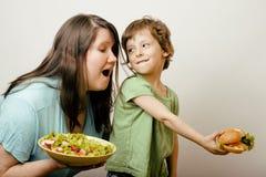 Mujer gorda que detiene la ensalada y al pequeño muchacho lindo con la hamburguesa Imagen de archivo libre de regalías