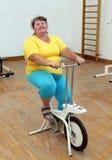 Mujer gorda que ejercita en el simulador de la bici Foto de archivo