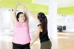 Mujer gorda que hace estirar con el instructor Imagen de archivo