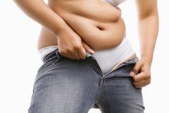 Mujer gorda que intenta poner sus pantalones vaqueros apretados Imagenes de archivo