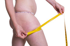 Mujer gorda que mide su pierna imagenes de archivo
