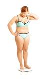Mujer gorda que se coloca en escala Fotos de archivo libres de regalías