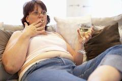 Mujer gorda que se relaja en el sofá Imagen de archivo libre de regalías