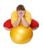 Mujer gorda que se sienta con la bola de la gimnasia Imágenes de archivo libres de regalías