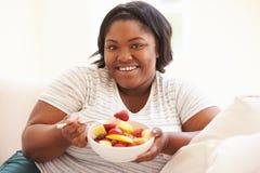 Mujer gorda que se sienta en la fruta de Sofa Eating Bowl Of Fresh Foto de archivo libre de regalías