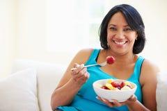 Mujer gorda que se sienta en la fruta de Sofa Eating Bowl Of Fresh Fotografía de archivo