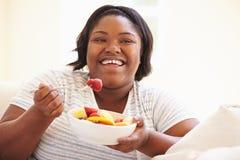 Mujer gorda que se sienta en la fruta de Sofa Eating Bowl Of Fresh imagenes de archivo