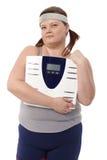 Mujer gorda que sostiene una escala disponible Imágenes de archivo libres de regalías