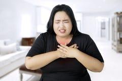 Mujer gorda que tiene un ataque del corazón en casa imagen de archivo libre de regalías