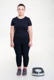 Mujer gorda seria que se coloca cerca de la balanza Imágenes de archivo libres de regalías