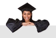 Mujer graduada que lleva a cabo el cartel Imagen de archivo libre de regalías
