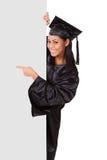 Mujer graduada que lleva a cabo el cartel Imágenes de archivo libres de regalías