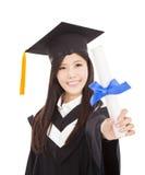 Mujer graduada sonriente que lleva a cabo grado Foto de archivo