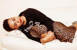 Mujer grande afroamericana bastante elegante de la mamá vestida bien el swag se relaja en casa, estampado leopardo en clothers fotos de archivo