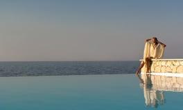 Mujer griega del estilo que se sienta en el borde de la piscina del infinito Imagenes de archivo