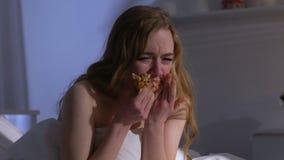 Mujer gritadora codicioso que come el cruasán en cama en la noche, problemas del peso, bulimia metrajes