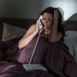 Mujer gritadora que llama el teléfono en cama Imagenes de archivo