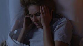 Mujer gritadora que miente en cama en la noche, cabeza de la tenencia, sufriendo de jaqueca almacen de metraje de vídeo