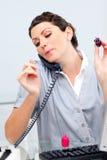 Mujer habladora en el teléfono que pinta sus clavos Foto de archivo