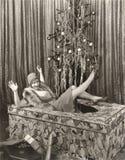 Mujer haciendo estallar fuera de la caja de regalo grande delante del árbol de navidad fotos de archivo