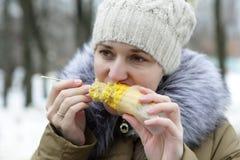 Mujer hambrienta que come maíz Imagenes de archivo
