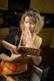 Mujer Harried con el libro de la receta Fotografía de archivo libre de regalías