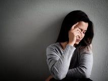 Mujer hearted rota deprimida que se sienta solamente en sitio oscuro foto de archivo