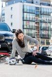 Mujer herida con el dolor severo causado por esguince de la rodilla después de accidente de la bicicleta foto de archivo libre de regalías