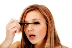 Mujer hermosa adolescente que aplica el rimel Fotografía de archivo