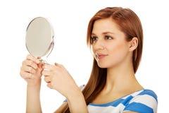 Mujer hermosa adolescente que mira en un espejo Fotografía de archivo