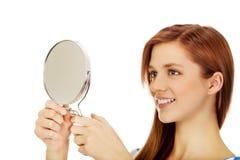 Mujer hermosa adolescente que mira en un espejo Foto de archivo libre de regalías