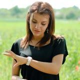 Mujer hermosa al aire libre que controla tiempo Imagen de archivo libre de regalías