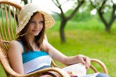 Mujer hermosa al aire libre que se relaja en silla de oscilación Foto de archivo