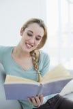Mujer hermosa alegre que lee un libro mientras que se sienta en el sofá Fotos de archivo libres de regalías