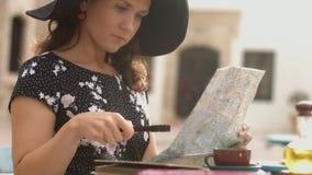 Mujer hermosa antes de viaje del planeamiento de las vacaciones de verano en el extranjero con el mapa almacen de metraje de vídeo
