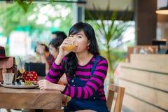 Mujer hermosa asiática joven que bebe el zumo de naranja fresco Imágenes de archivo libres de regalías