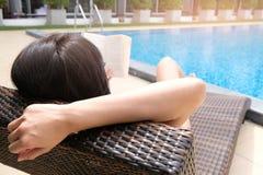 Mujer hermosa asiática joven que se relaja en la piscina que miente en a imagenes de archivo