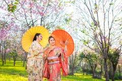 Mujer hermosa asiática que lleva el kimono y la flor de cerezo japoneses tradicionales en la primavera, Japón fotografía de archivo libre de regalías