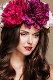 Mujer hermosa atractiva con las flores brillantes en su cabeza Foto de archivo libre de regalías