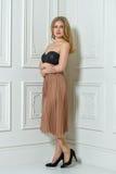 Mujer hermosa, atractiva en el vestido de noche que presenta cerca de la pared texturizada Foto de archivo libre de regalías