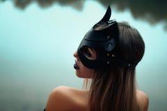Mujer hermosa atractiva en máscara del gato negro imágenes de archivo libres de regalías