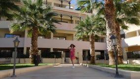 Mujer hermosa atractiva que camina hacia la c?mara en el jard?n del hotel que lleva la presentaci?n roja del vestido, del sombrer almacen de video