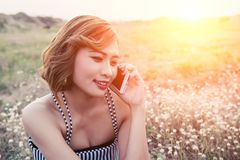 Mujer hermosa atractiva que habla en smartphone en campo de flor Foto de archivo libre de regalías