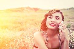 Mujer hermosa atractiva que habla en smartphone en campo de flor Imagen de archivo