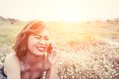Mujer hermosa atractiva que usa un smartphone en campo de flor en summe Imagen de archivo