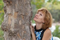 Mujer hermosa cerca del árbol Foto de archivo libre de regalías