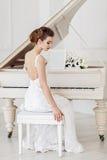 Mujer hermosa cerca del piano blanco Fotos de archivo libres de regalías